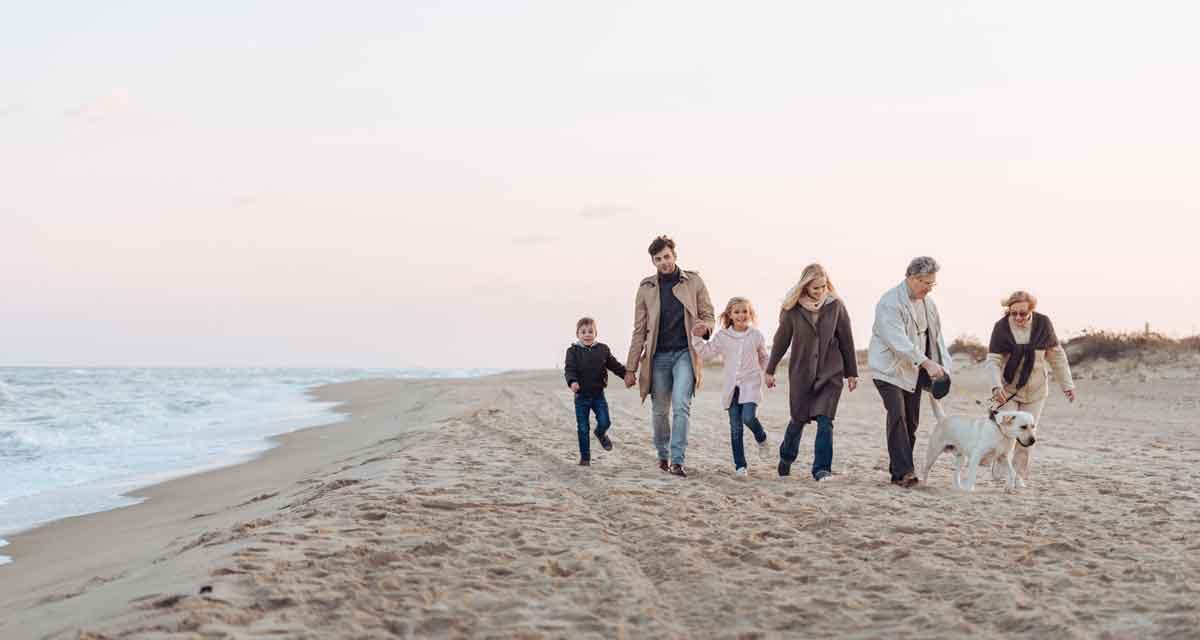 familiewandeling op het strand met hond